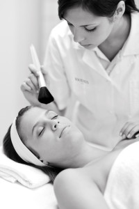 Luxury facial care - woman in spa salon with beautician receiving beauty treatment